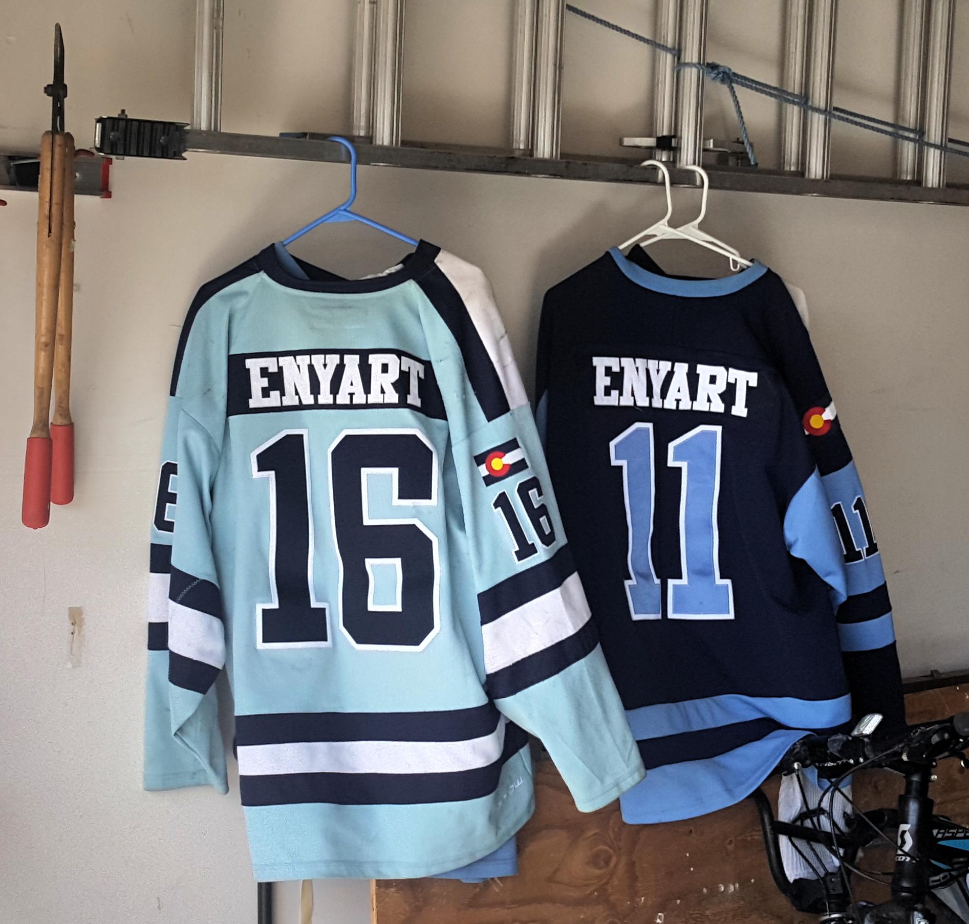 1611 KJV Debate photo of Enyart sons hockey jerseys, #16 & #11, handing in the garage